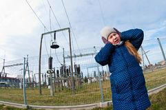 Girl standing near a power station, bad influence on people concept royalty free stock photo