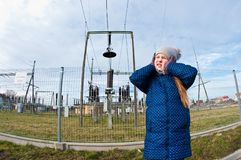 Girl standing near a power station, bad influence on people concept stock photo
