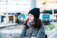 Girl standing near the railway station trying to hold back her tears - close up side view with closed eyes Stock Photography