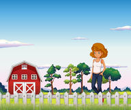 A girl standing near the red barnhouse inside the fence Stock Images