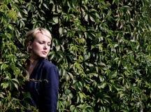 Girl standing near the shrub Royalty Free Stock Photos