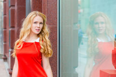 Girl standing near the store window Royalty Free Stock Photography