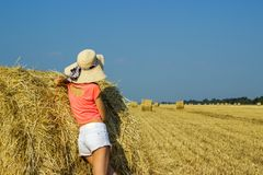The girl is standing near a straw bale and looking into the distance in the field.  Stock Images