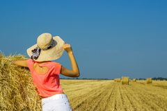 The girl is standing near a straw bale and looking into the distance in the field.  Stock Image