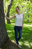 Girl standing near the tree. In the park Stock Photography