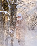 Girl standing near tree snow falls Royalty Free Stock Photo