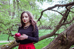 Girl standing near a tree trunk. Girl in a red skirt standing near a tree trunk with apple in hand Royalty Free Stock Image