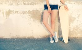 Girl Standing Near Wall With Her Legs Crossed Holding Her Longboard Leaning Back Weared Wall, A Lot Of Copyspace Royalty Free Stock Images