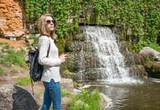 Girl standing near a waterfall in a park Stock Photos