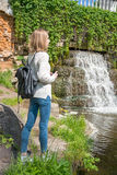 Girl standing near a waterfall in a park Royalty Free Stock Image