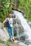 Girl standing near a waterfall in a park Stock Images