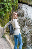 Girl standing near a waterfall in a park Royalty Free Stock Photo