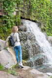 Girl standing near a waterfall in a park Stock Image