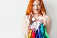 Red-haired woman holding hangers with colored clothes stock photography