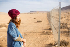 Girl standing next metal fencing. Stock Photo