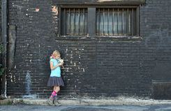 Girl standing next to brick wall Stock Images