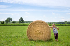 Girl Standing Next to Hay Bale in a Green Field stock photography