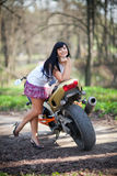 A girl is standing next to a motorcycle. Biker girl is standing next to a motorcycle. beautiful black-haired woman in a short skirt standing near a sports bike Royalty Free Stock Images