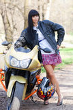 A girl is standing next to a motorcycle. Biker girl is standing next to a motorcycle. beautiful black-haired woman in a short skirt standing near a sportsbike Stock Image