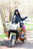 A girl is standing next to a motorcycle. Biker girl is standing next to a motorcycle. beautiful black-haired woman in a short skirt standing near a sportsbike Royalty Free Stock Photo