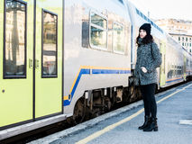 Girl standing next to a train and looking forewards Stock Image
