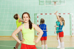 Girl standing next to the volleyball net in gym Royalty Free Stock Images
