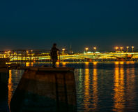 Girl standing at night on city dock and admires the view of illumination city Royalty Free Stock Photo