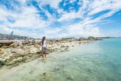 Girl standing in the ocean ansd sadly looking far away at garbage dump Stock Images