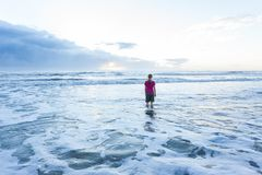 Girl Standing in Ocean at Sunrise. Young lady standing in ocean at the beach wearing shorts and t-shirt, with blonde hair. It is sunrise, and the sun is stock photography