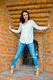 Girl standing at the old brick wall Stock Images