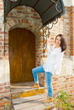 Girl standing at the old wooden door Stock Photo