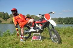 Girl standing on one foot, the other on the bike. Girl in sports uniform for motocross leaned back standing on one foot, the other placing on the bandwagon Stock Photography
