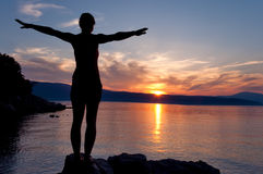 Girl standing with open arms on sea sunset at Glavotok - Croatia Stock Image
