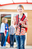 Girl Standing Outside School With Rucksack Stock Photo