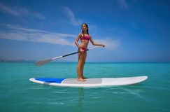 Girl standing on paddle surf board SUP. In summer royalty free stock photography