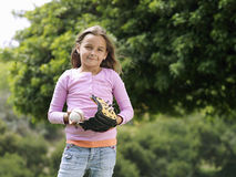 Girl (7-9) standing in park with baseball and glove, smiling, front view, portrait Royalty Free Stock Photo