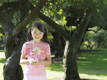 Girl (7-9) standing in park near trees, listening to MP3 player, smiling, front view, portrait Royalty Free Stock Images