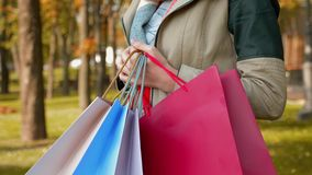 A girl is standing in the park with purchases in multi-colored paper bags stock video