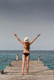 Girl standing at the pier raising her arms to the sky Stock Photos