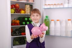 Girl standing with piggy bank money box on the refrigerator background. Young beautiful girl standing with piggy bank money box on the refrigerator background Royalty Free Stock Images