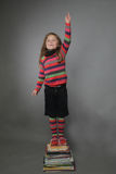 Girl standing on pile of books Royalty Free Stock Photography