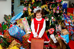 Girl Standing in a Pile of Christmas Presents Holding a Box Stock Photos