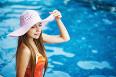 Girl standing by a poolside Stock Images