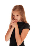 Girl standing in profile and praying. Royalty Free Stock Image
