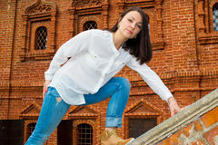 Girl standing on the railing of a stone staircase Royalty Free Stock Photography