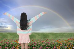 Girl standing and raising her hands in front of rainbow curve. Royalty Free Stock Photos