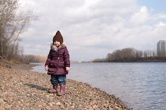 Girl standing on a riverbank Royalty Free Stock Photos