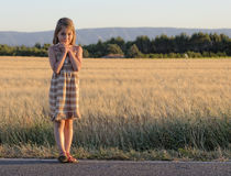 Girl standing at roadside Stock Image