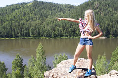 Girl standing on a rock and enjoying river  view Stock Photo