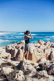 Girl Standing on Rock Formations With Hand Covering Eyes from Sun Light Near Body of Water Royalty Free Stock Photos